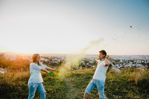 Homme et femme jouent avec de la fumée colorée debout sur la pelouse verte Photo gratuit