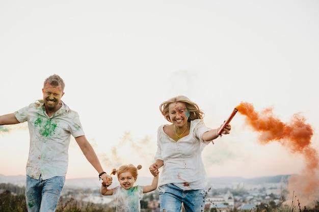 Homme, femme et leur petite fille s'amusent à courir avec de la fumée colorée dans les bras Photo gratuit