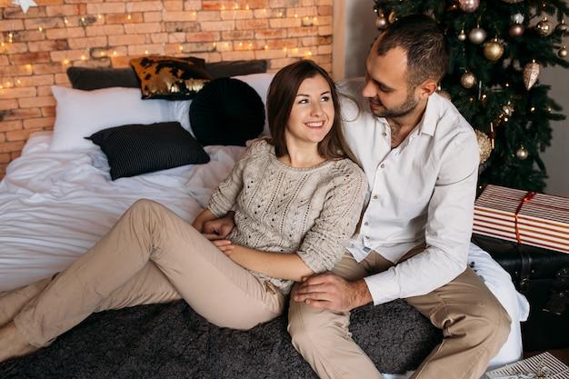 Homme et femme à la maison près de sapin de noël. couple amoureux au lit Photo Premium