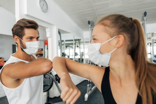 Homme Et Femme Avec Des Masques Médicaux Faisant Le Salut Du Coude à La Salle De Sport Photo gratuit