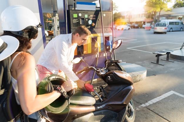 Homme et femme de motocyclistes à la station couple couple vélo pertol Photo Premium