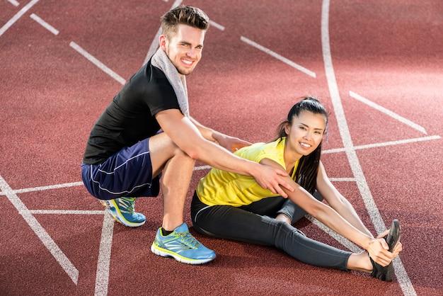 Homme et femme sur une piste de cendres de sports stretching arena Photo Premium