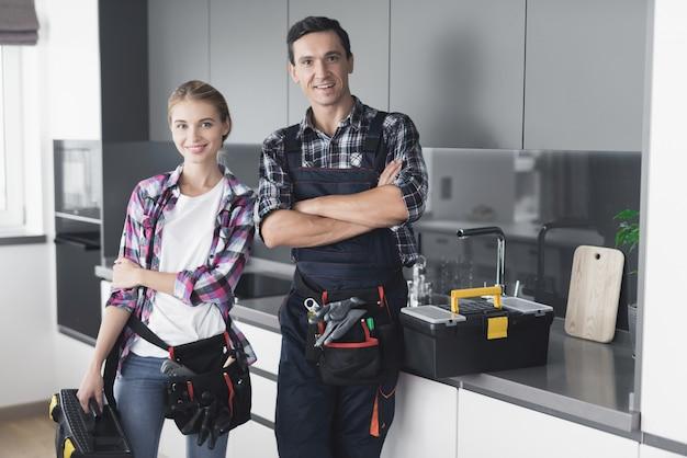 Un homme et une femme plombier sont debout dans la cuisine. Photo Premium