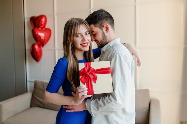 Homme Et Femme Avec Présent Dans Une Boîte Cadeau Avec Des Ballons En Forme De Coeur Rouge à La Maison Photo Premium