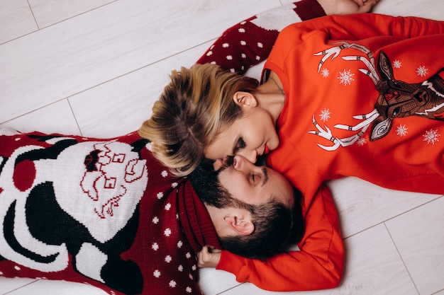 Homme et femme en pulls de noël s'embrassent tendue sur le sol Photo gratuit