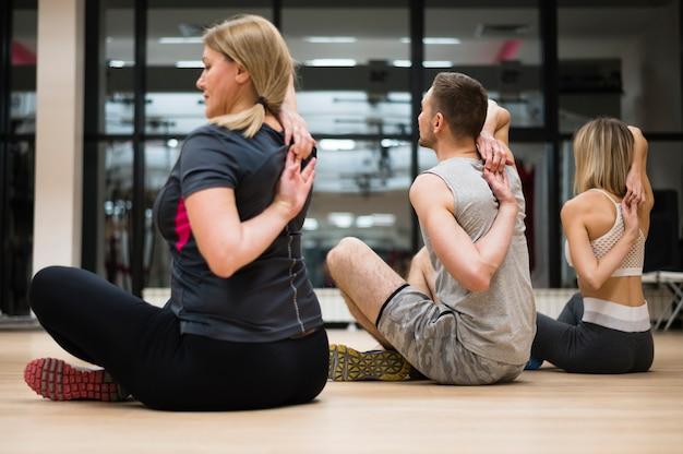 Homme et femme qui s'étirent ensemble à la gym Photo gratuit