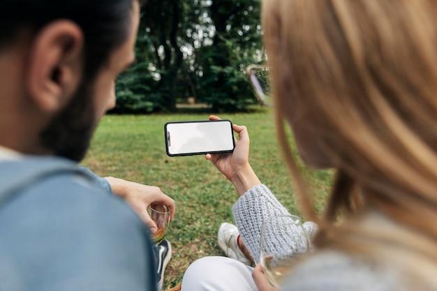 Homme Et Femme Regardant Un Téléphone Tout En Ayant Un Pique-nique En Plein Air Photo gratuit