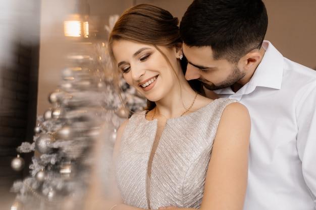 Un homme et une femme en robe argentée s'embrassent devant un arbre de noël Photo gratuit
