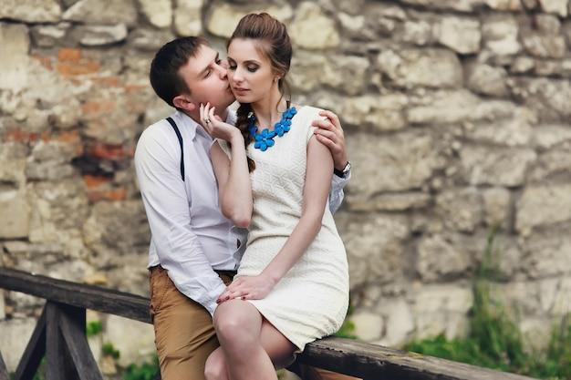 L'homme et la femme s'embrassent assis sur les mains courantes en bois Photo gratuit