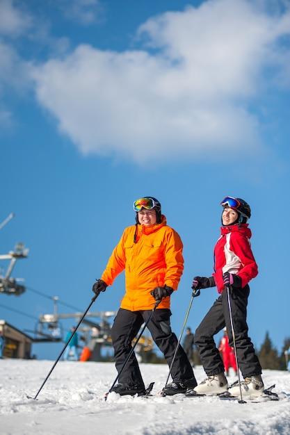 Homme et femme de skieurs avec des skis dans la station de sports d'hiver Photo Premium