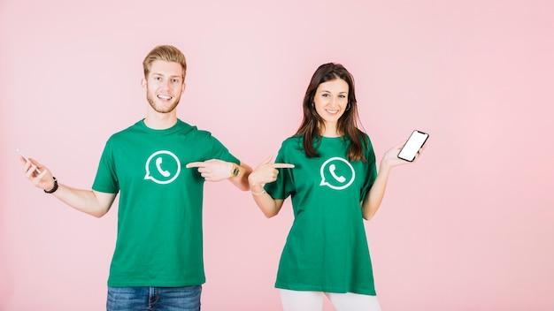 Homme et femme avec téléphone portable pointant sur leur t-shirt avec l'icône whatsapp Photo gratuit