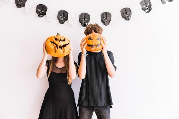 Homme et femme tenant des citrouilles avant les visages Photo gratuit