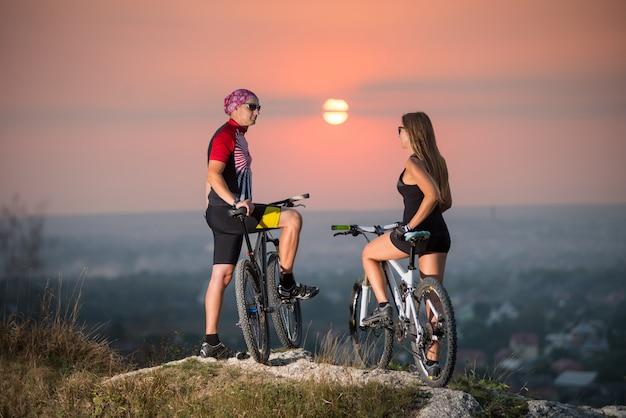 Homme et femme sur un vélo de montagne, debout sur les rochers de la falaise, se retournant vers la caméra. Photo Premium