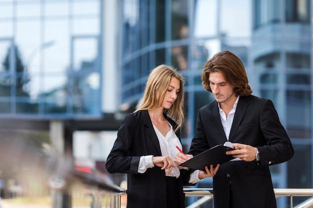 Homme et femme vérifiant un presse-papiers Photo gratuit