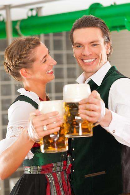 Homme et femme avec verre à bière dans une brasserie Photo Premium