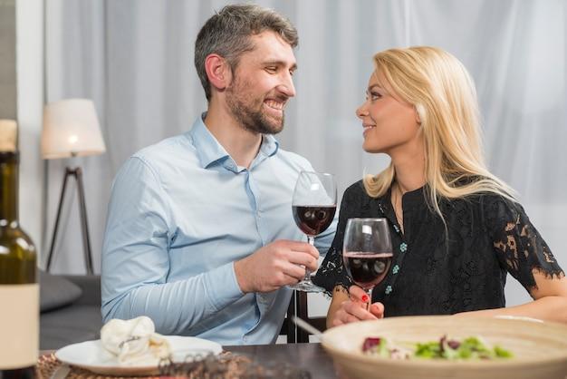 Homme et femme avec des verres de boisson à table avec bol de salade Photo gratuit