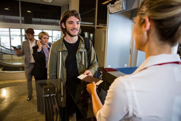 Homme En File D'attente Recevant Un Passeport Et Une Carte D'embarquement Photo gratuit