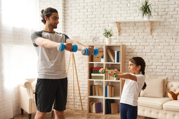 Homme et fille, faire des exercices avec des haltères. Photo Premium