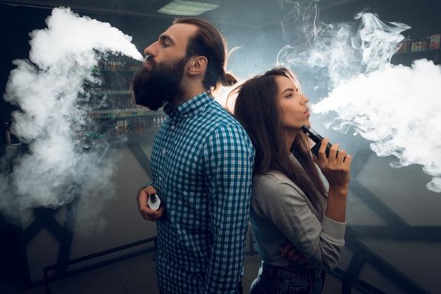 Un homme et une fille fument et se détendent dans une discothèque. Photo Premium