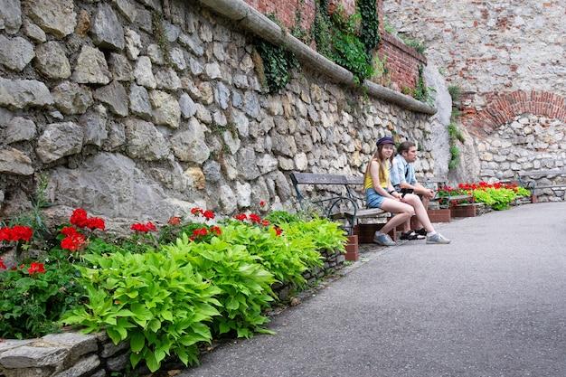 Un homme et une fille sont assis sur un banc dans le parc contre un mur de pierre. Photo Premium