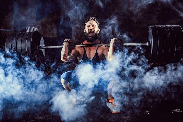 Homme de fitness musclé faisant deadlift une barre de poids sur sa tête dans un centre de fitness moderne. entraînement fonctionnel. Photo Premium