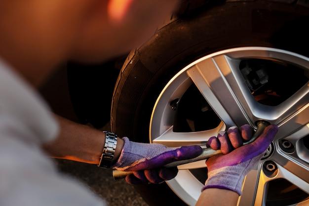 Homme fixant les boulons de roue Photo gratuit