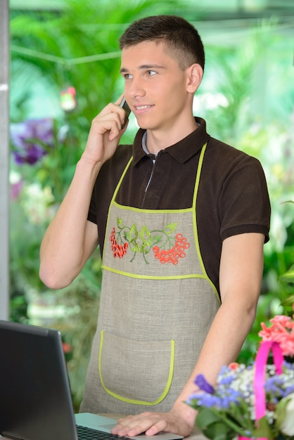 Homme fleuriste travaillant avec des fleurs dans une serre. Photo Premium