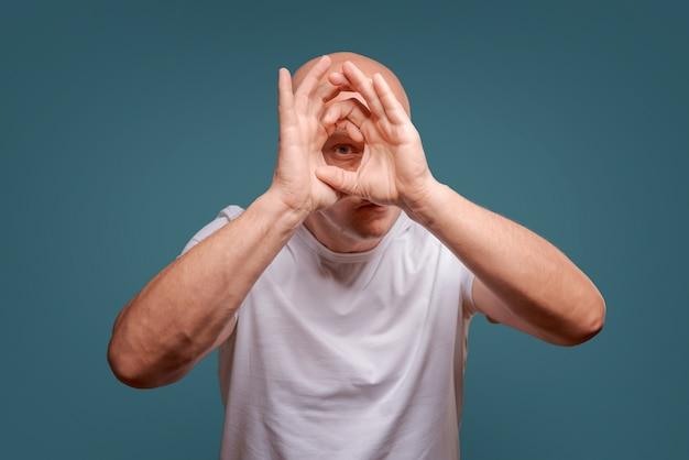 Un homme sur un fond bleu en tenant ses mains près de ses yeux comme un télescope Photo Premium