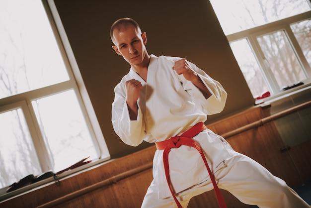 Homme Fort Combattant D'arts Martiaux En Mouvements D'entraînement Blancs. Photo Premium