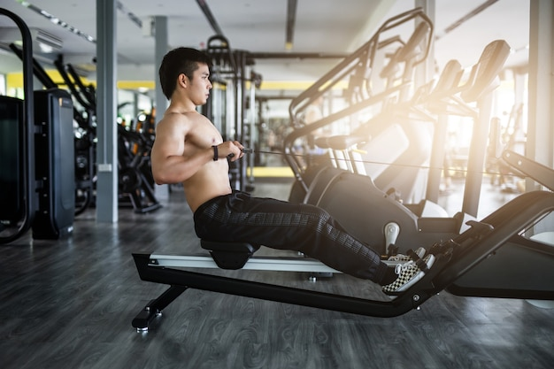 Homme fort exerce dans la salle de fitness. Photo Premium