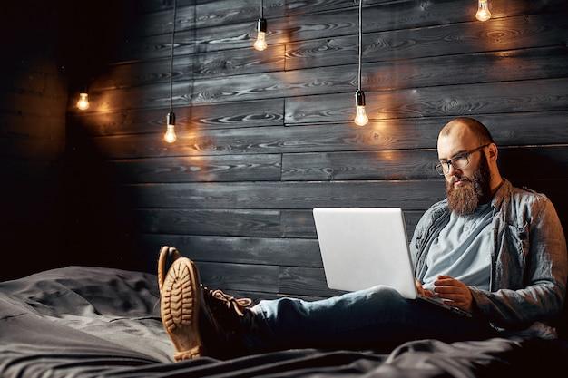 Homme de freelancer réussi avec barbe de style de vie atteint un nouvel objectif avec un ordinateur portable à l'intérieur du loft Photo Premium
