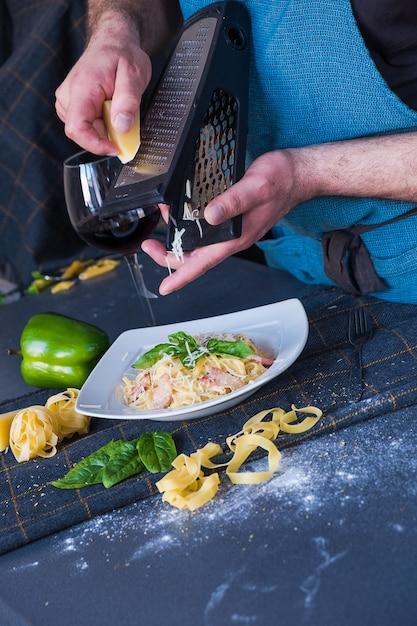 L'homme Frotte Le Fromage Sur Les Pâtes Avec Bacon, Crème, Basilic, Parmesan Sur Une Plaque Blanche. Photo Premium