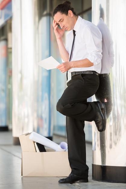 Un homme frustré en costume, debout près du bureau. Photo Premium
