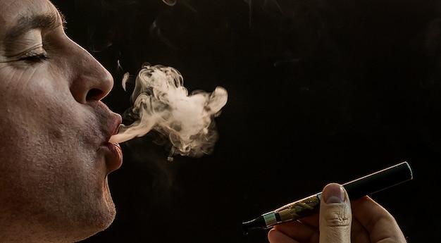 Homme Fumant Cigarette Sur Fond Noir, Beau Jeune Homme Fumant Cigarette, Homme Mystère Avec Cigare Et Fumée Isolé Sur Fond Noir Photo gratuit