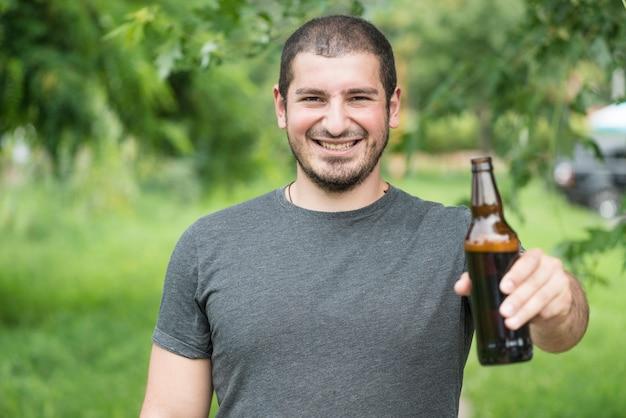Homme gai acclamant avec bouteille à caméra Photo gratuit