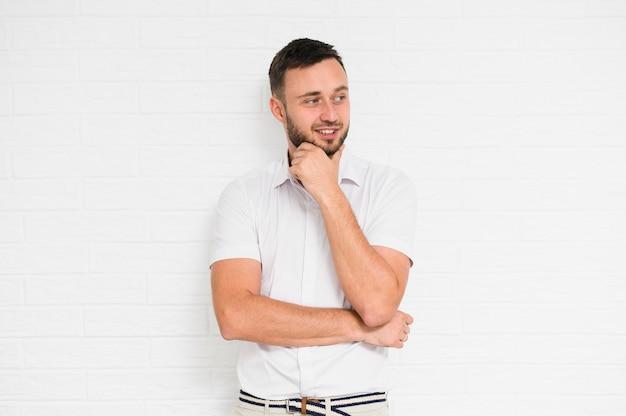 Homme gai se penchant le menton avec la main gauche Photo gratuit