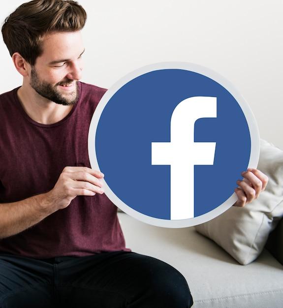 Homme gai tenant une icône facebook Photo gratuit