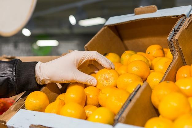 Un Homme En Gants Blancs Dans Un Magasin Achète De La Nourriture. L'homme Tient Une Orange Dans Ses Mains Photo Premium