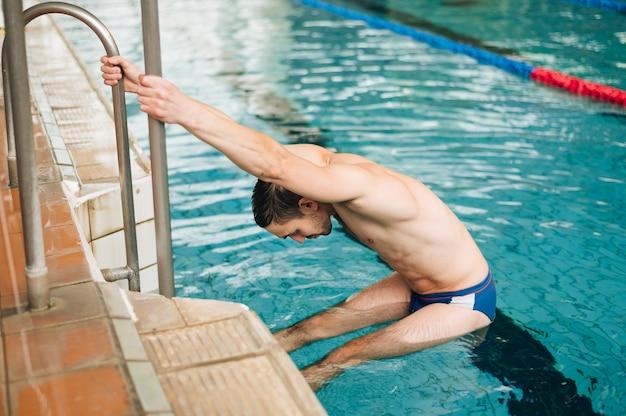 Homme grand angle, sur, escalier piscine Photo gratuit