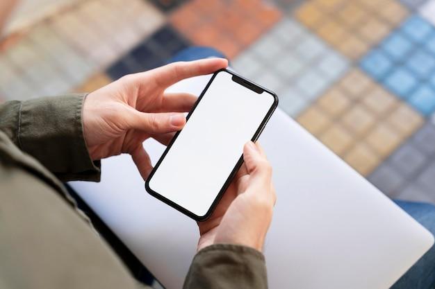 Homme Grand Angle Regardant Son Téléphone Avec écran Vide Photo gratuit