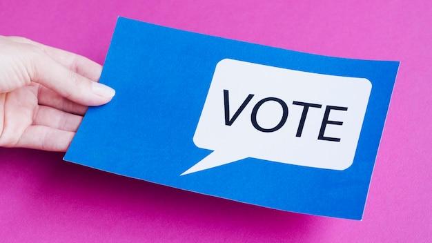 Homme grand angle tenant une carte bleue avec bulle de vote Photo gratuit