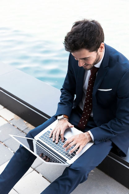 Homme grand angle travaillant sur un ordinateur portable près du lac Photo gratuit