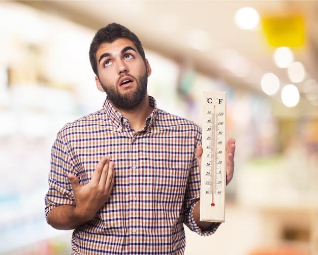 L'homme avec un grand thermomètre dans une main Photo gratuit
