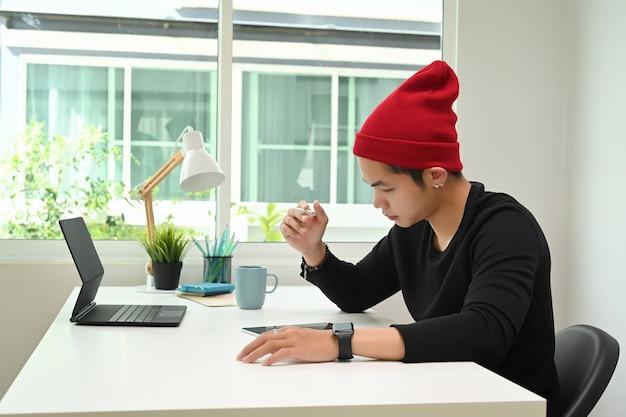 Un Homme Graphiste En Chapeau De Laine Rouge Travaille Sur Une Tablette Graphique Au Bureau Au Bureau Photo Premium