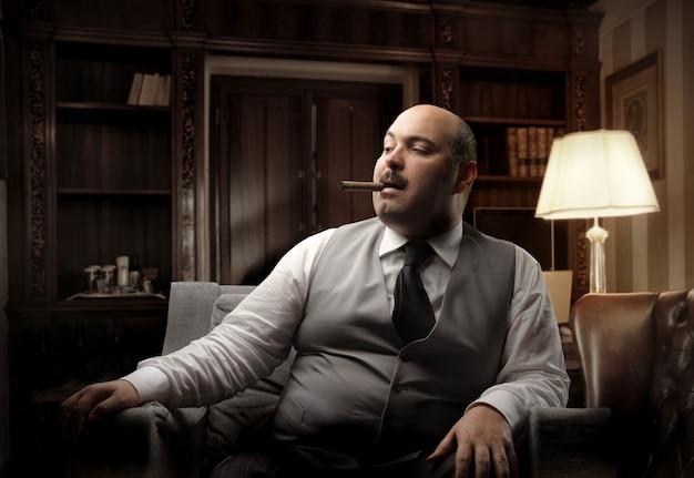 Homme gras riche fumant un cigare Photo Premium
