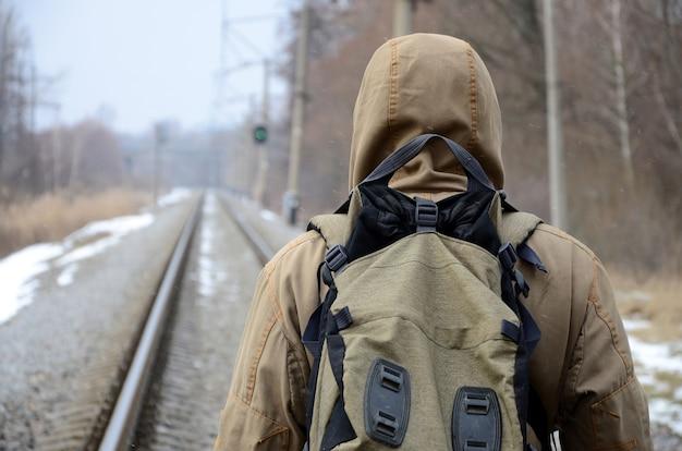 Un homme avec un gros sac à dos s'en va sur le chemin de fer Photo Premium