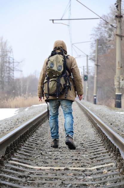 Un homme avec un gros sac à dos s'en va sur la voie ferrée Photo Premium
