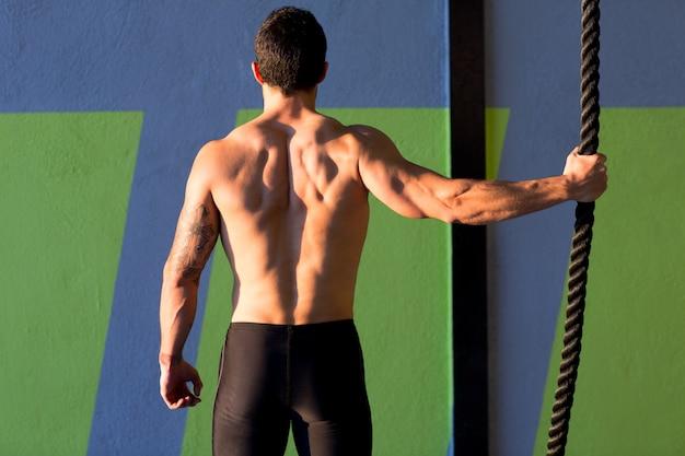 Homme de gym crossfit tenant à la main une corde d'escalade Photo Premium