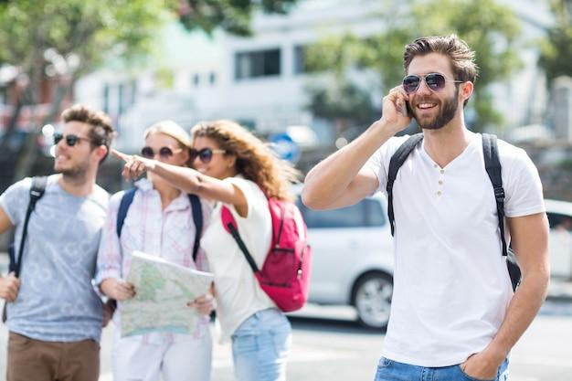 Homme de la hanche sur appel téléphonique et des amis en regardant la carte Photo Premium