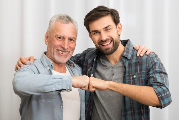 Homme heureux âgé, cogner les poings et étreindre avec un jeune homme souriant Photo gratuit